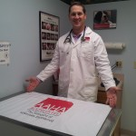 Darren Taul, DVM of Lancaster Veterinary Center in Lancaster KY., shows off his customized Ezee~Visit Pet Vet Mat w/ AAHA logo.